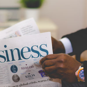 hands holding business newspaper