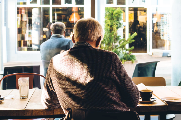 man in sweater sitting at a cafe facing away