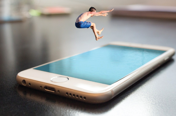 person in swim trunks leaping into blue iphone