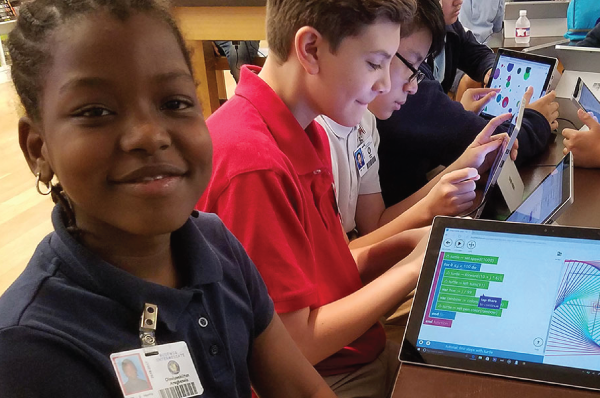 young people using tablets to learn coding