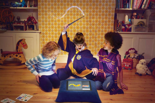 three children surrounding a tablet and the center child waving a wand